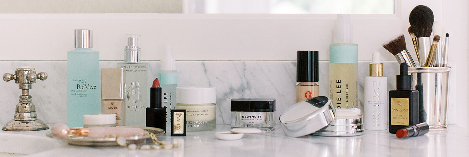 an array of beauty products on a bathroom sink